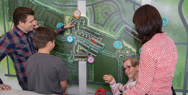 Clare and her family looking at the Shawnee Park community map together