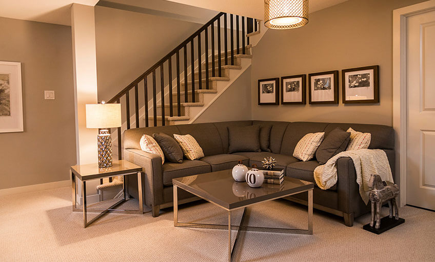 Living room phorograph with L shaped sectional couch next to staircase lit by warm lighting
