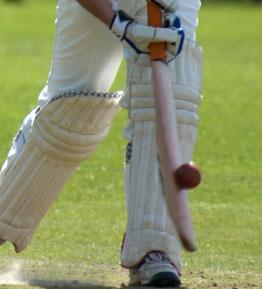 Cricket player hitting a ball