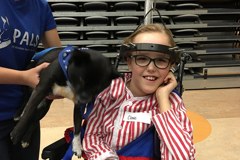 Clare and a cute dog in a gymnasium