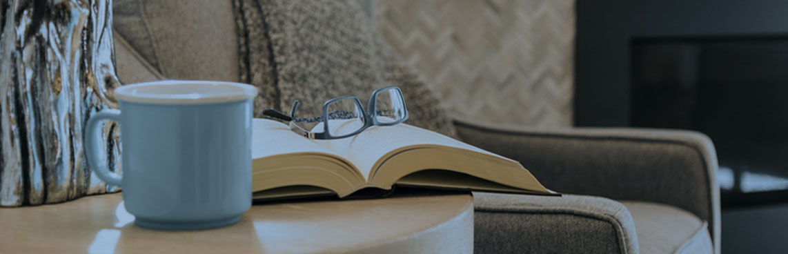 Photo of a coffee mug, glasses, a book and a comfy chair