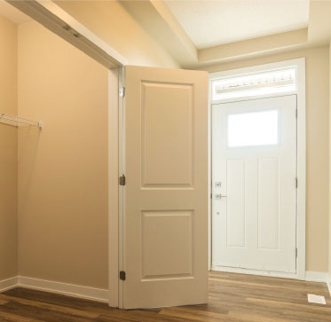 Front-hall walk-in closet with double swing doors accommodates easily accessible storage space