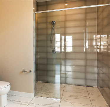 A curbless floor-to-ceiling glass walk-in shower with floor tiles that slope toward a drain provides an easy-to-clean, accessible grooming environment